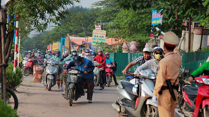 Cảnh sát giao thông hướng dẫn người dân dắt xe ngược chiều trên vỉa hè
